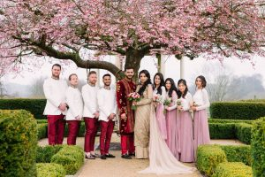 Asian Wedding Photography of bride and groom, groomsmen and bridesmaids under cherry blossom at Froyle Park