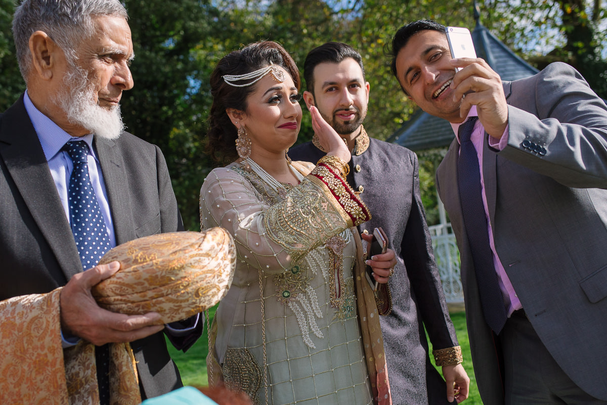 Photography of relatives calling at Asian wedding at Alton House Hotel