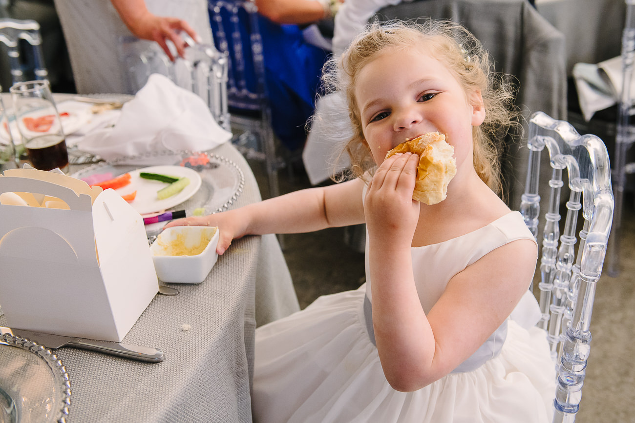 Cheeky flower girl in white dress eating bread at Russets Country House