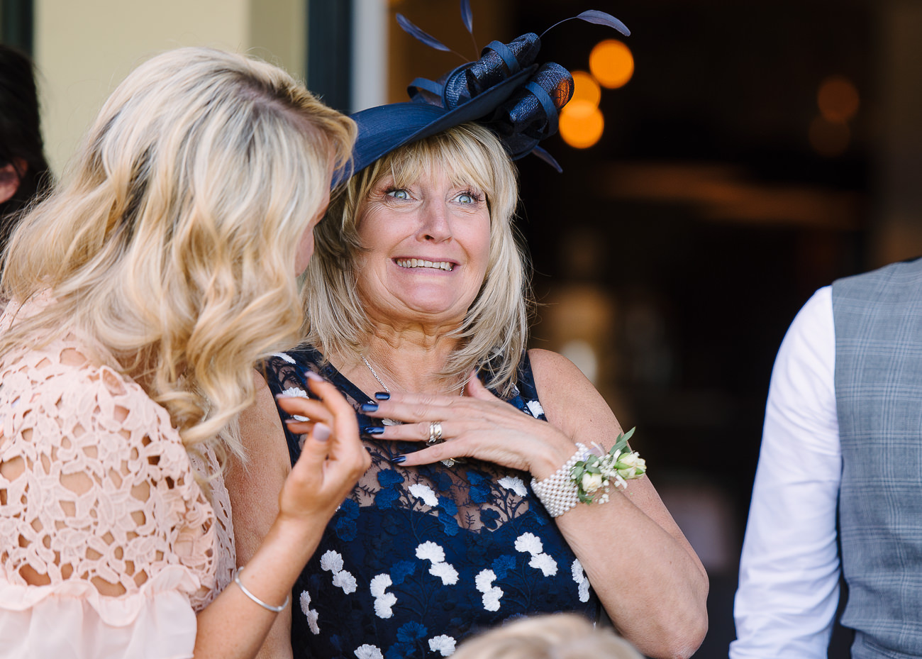 Mother of the groom pulling a face after a guest whispered something in her ear