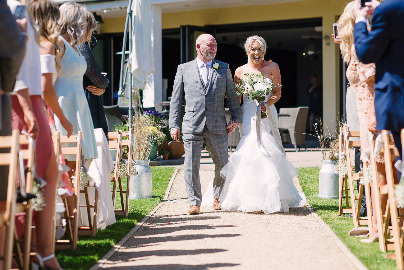 Happy bride walking down the isle with dad during outdoor ceremony at Russets