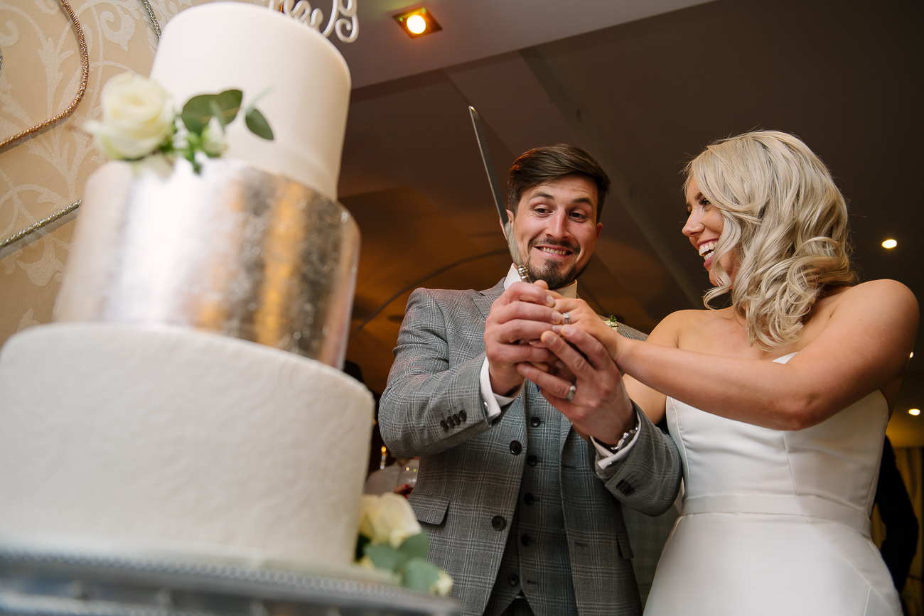 Bride and groom preparing to cut a big cake in front of the guests at Russets Country House