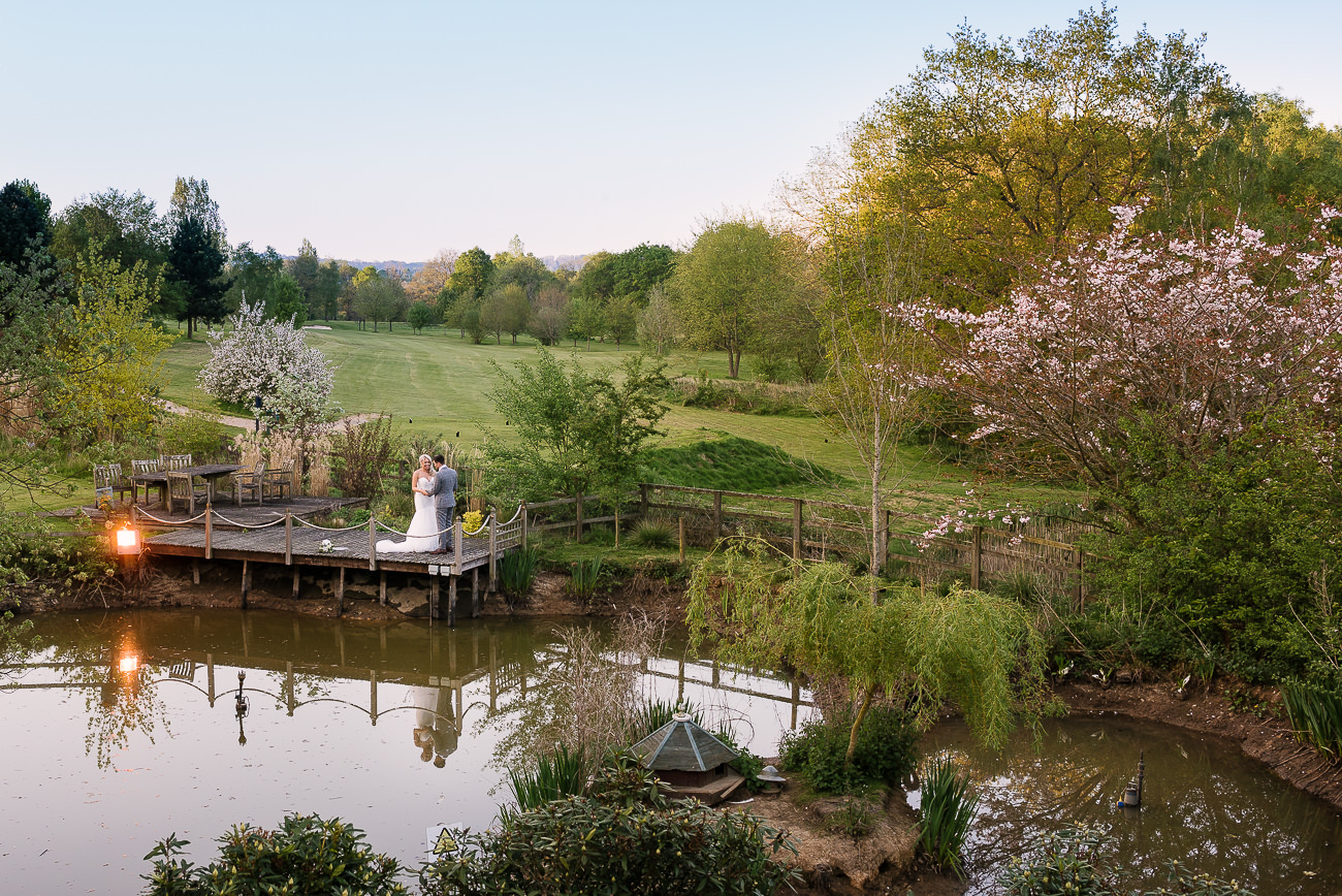 Wide photograph of the bride and groom standing by the Russets pond at sunset overlooking the grounds at Russets