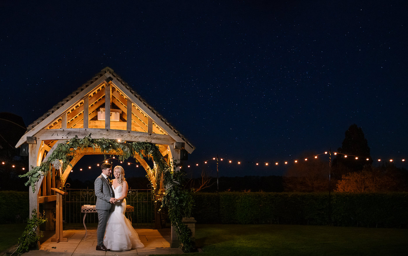Night time portrait of bride and groom with festoon lights at Russets Country House
