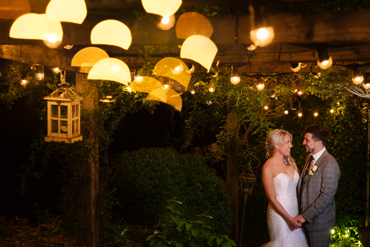 Bride and groom holding hands in the evening under the festoon lights at Russets Country House