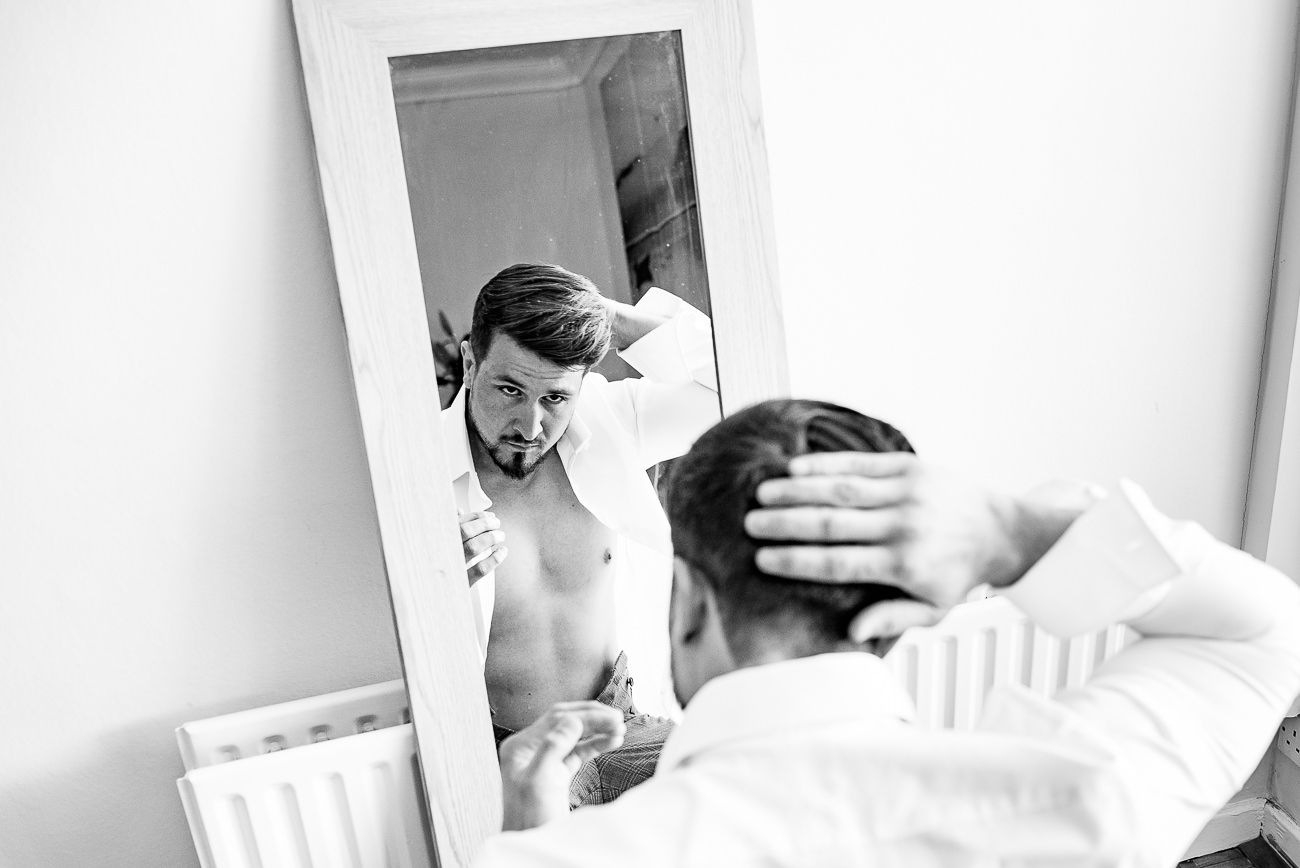 Groom doing his hair done in front of a mirror