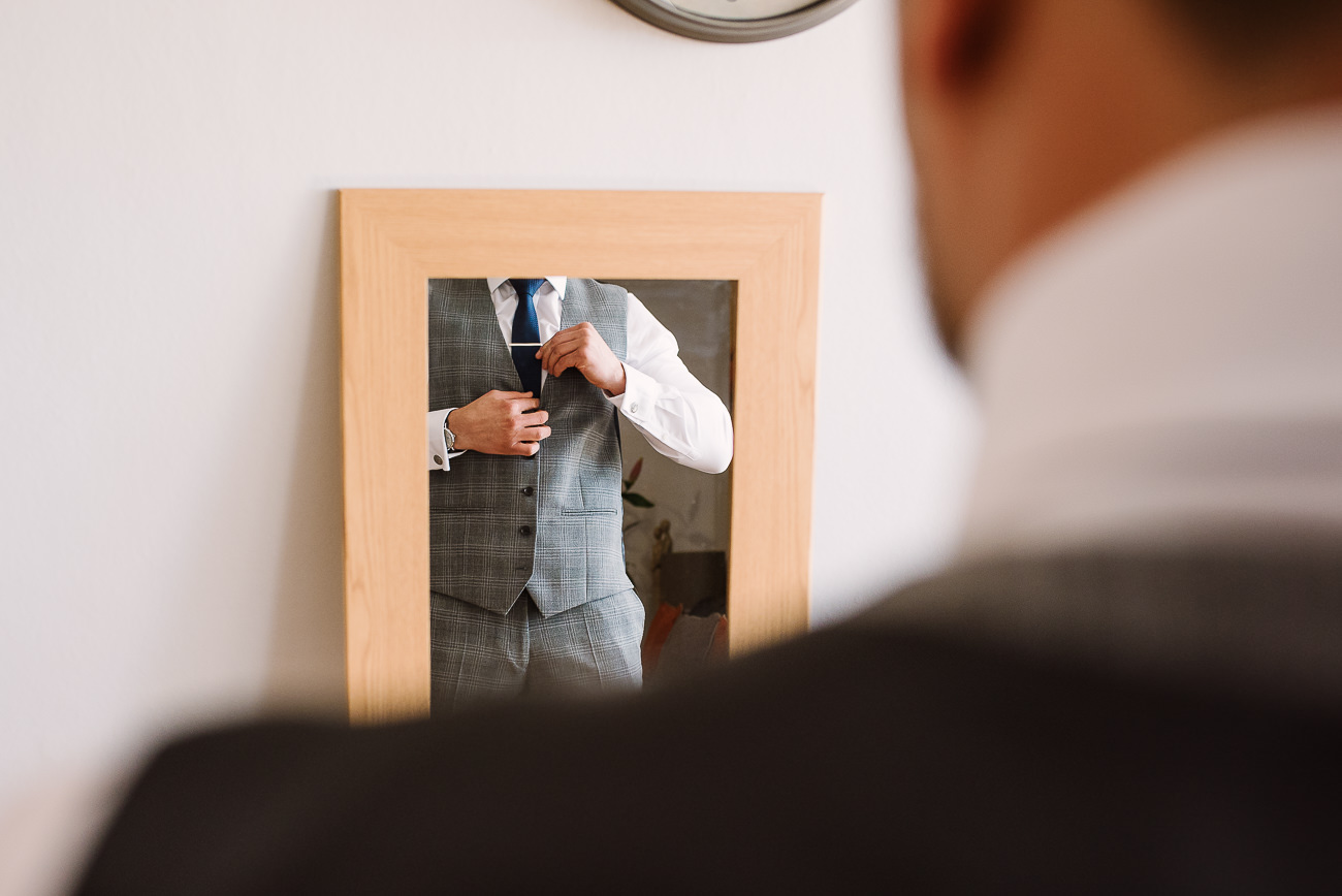 Groom arranges his tie in the mirror