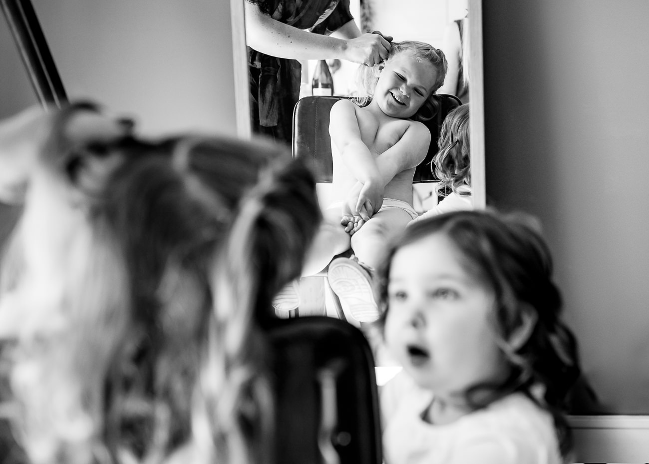 Flower girls having hair done, one looking amazed
