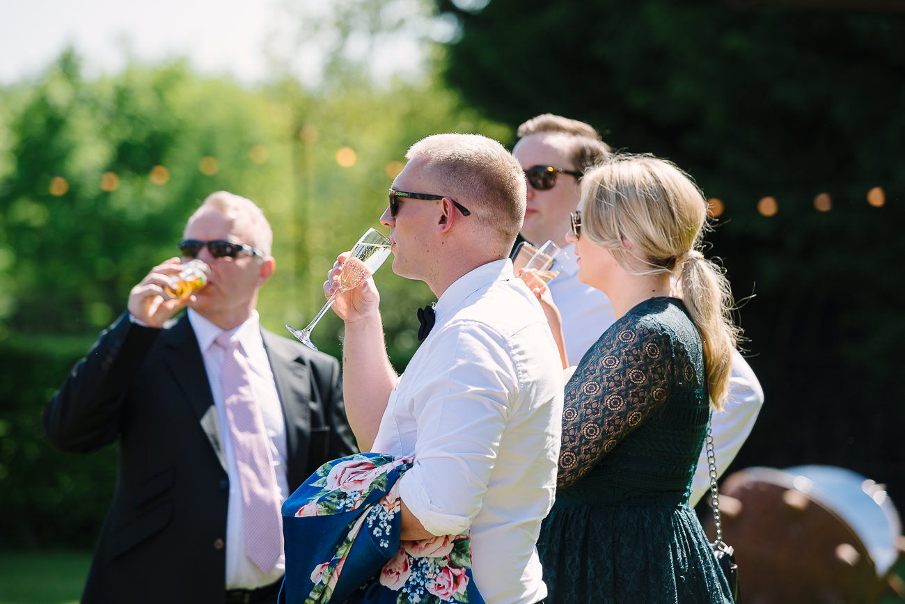 Wedding guests sipping drinks and enjoying the grounds at Russets Country House