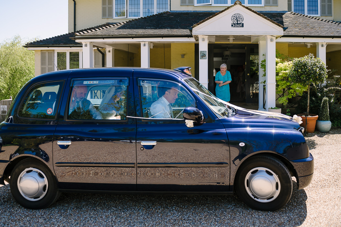 Bride arrives at Russets Country House in a blue cab car