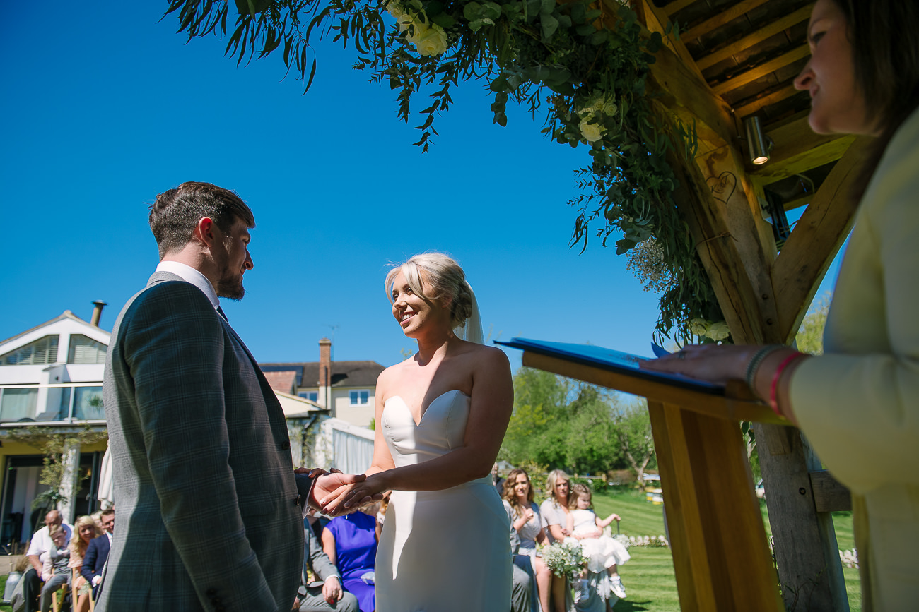 Groom and bride are smiling to each other during outdoor ceremony