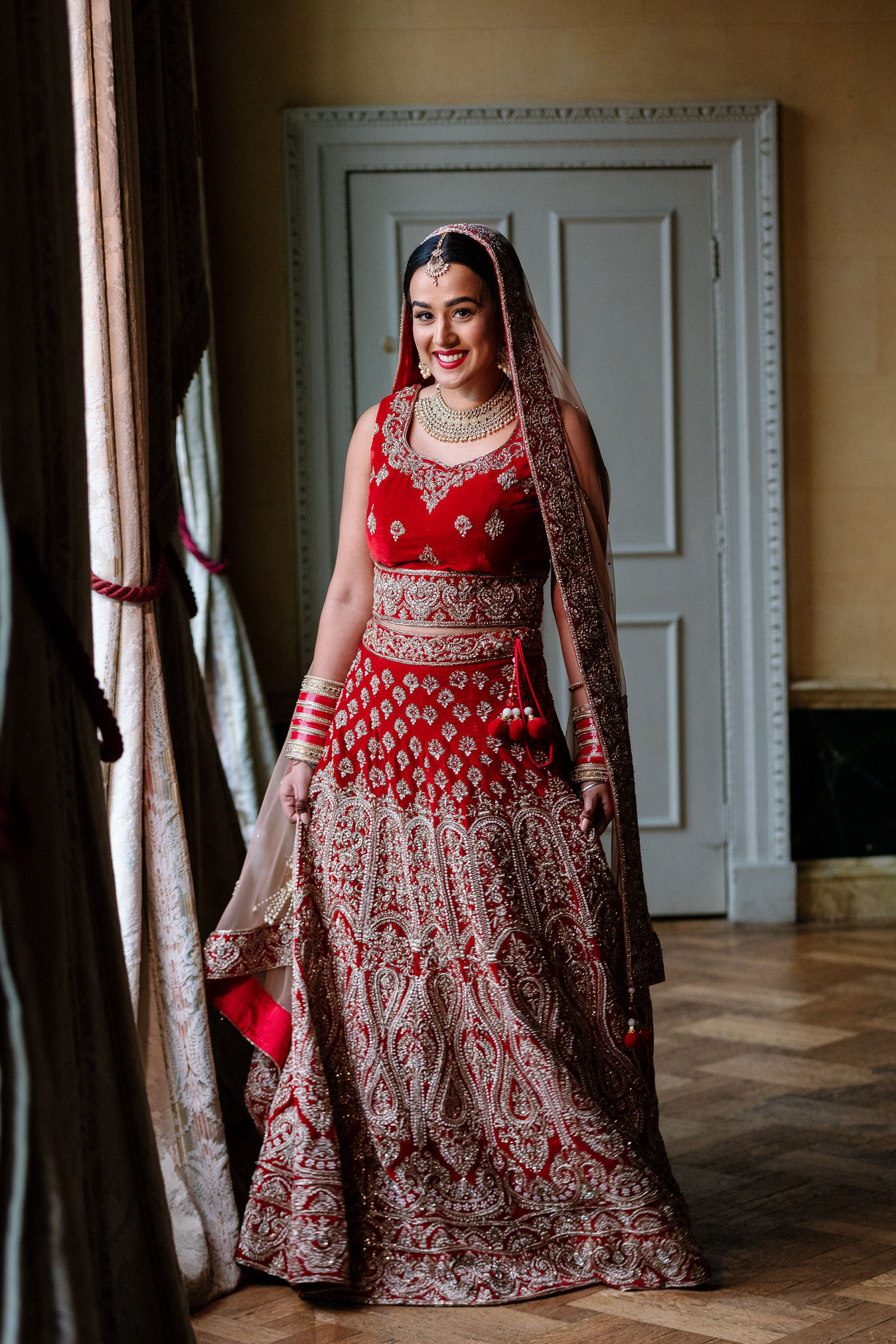 Asian Sikh bride dressed in a red bridal lehenga with golden details smiling in natural light.
