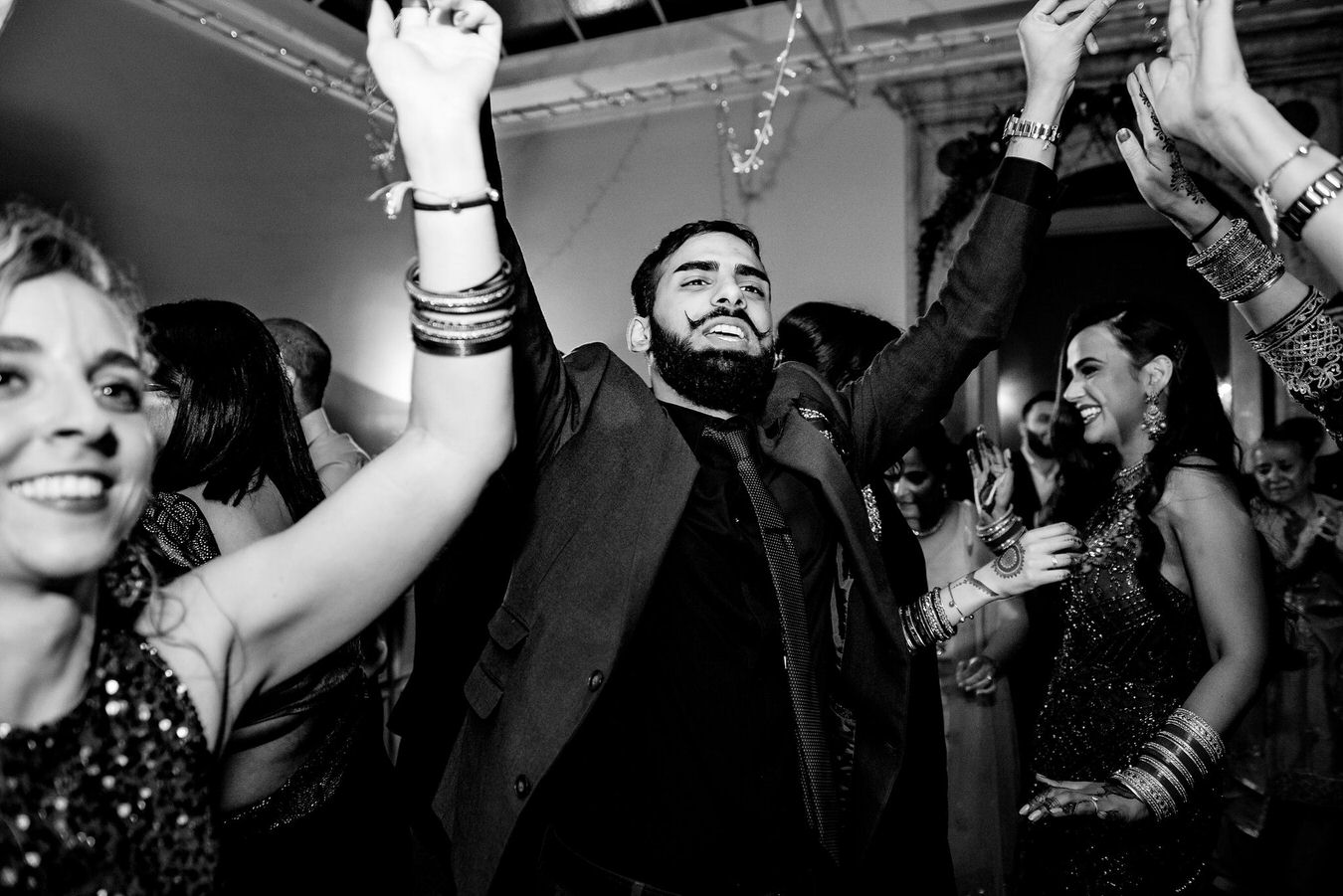 Asian wedding guests feel good dancing with the hands up and singing