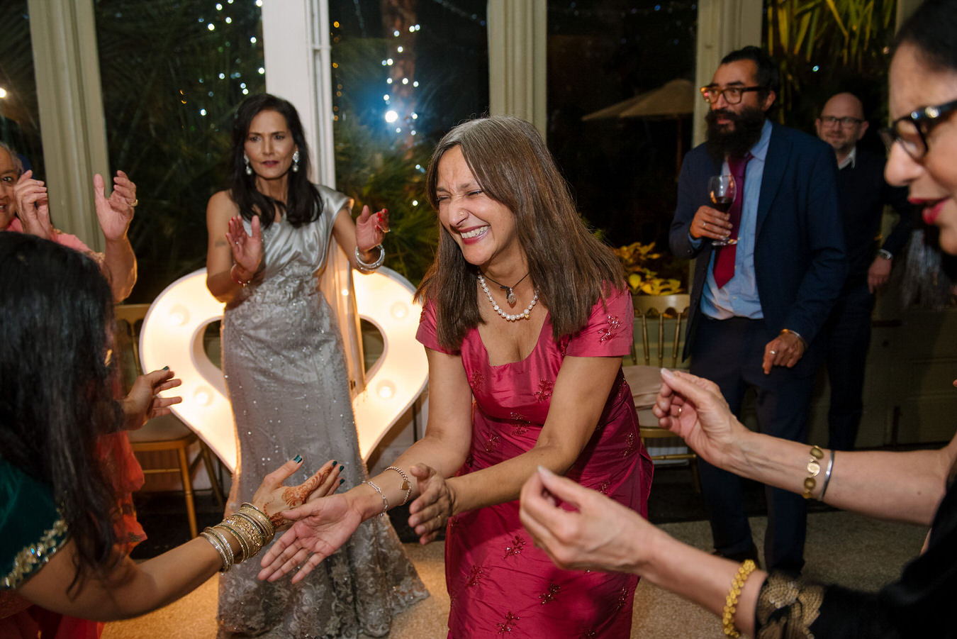Wedding guests are clapping hands in the rhythm of the Asian music and dance.