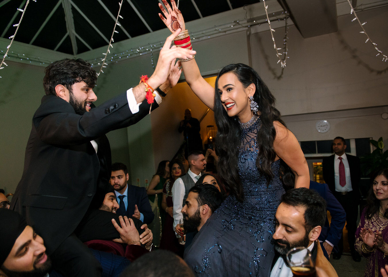 Sikh Asian bride and groom with hands in the air, singing and dancing on the guests shoulders.