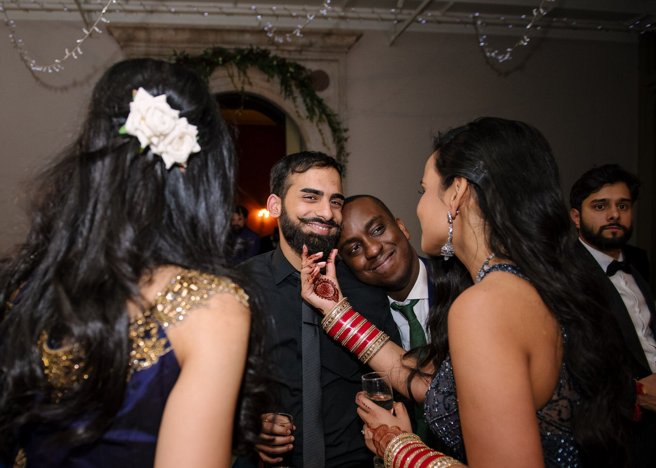 Documentary Asian wedding photographer captures a moment between the bride and one of her friends, the bride is touching her friend's beard.