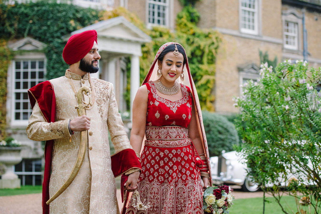 Sikh bride in a bridal long lehenga with Sikh groom in a Punjabi outfit with his kirpan in right hand walking in front of Hampton Court