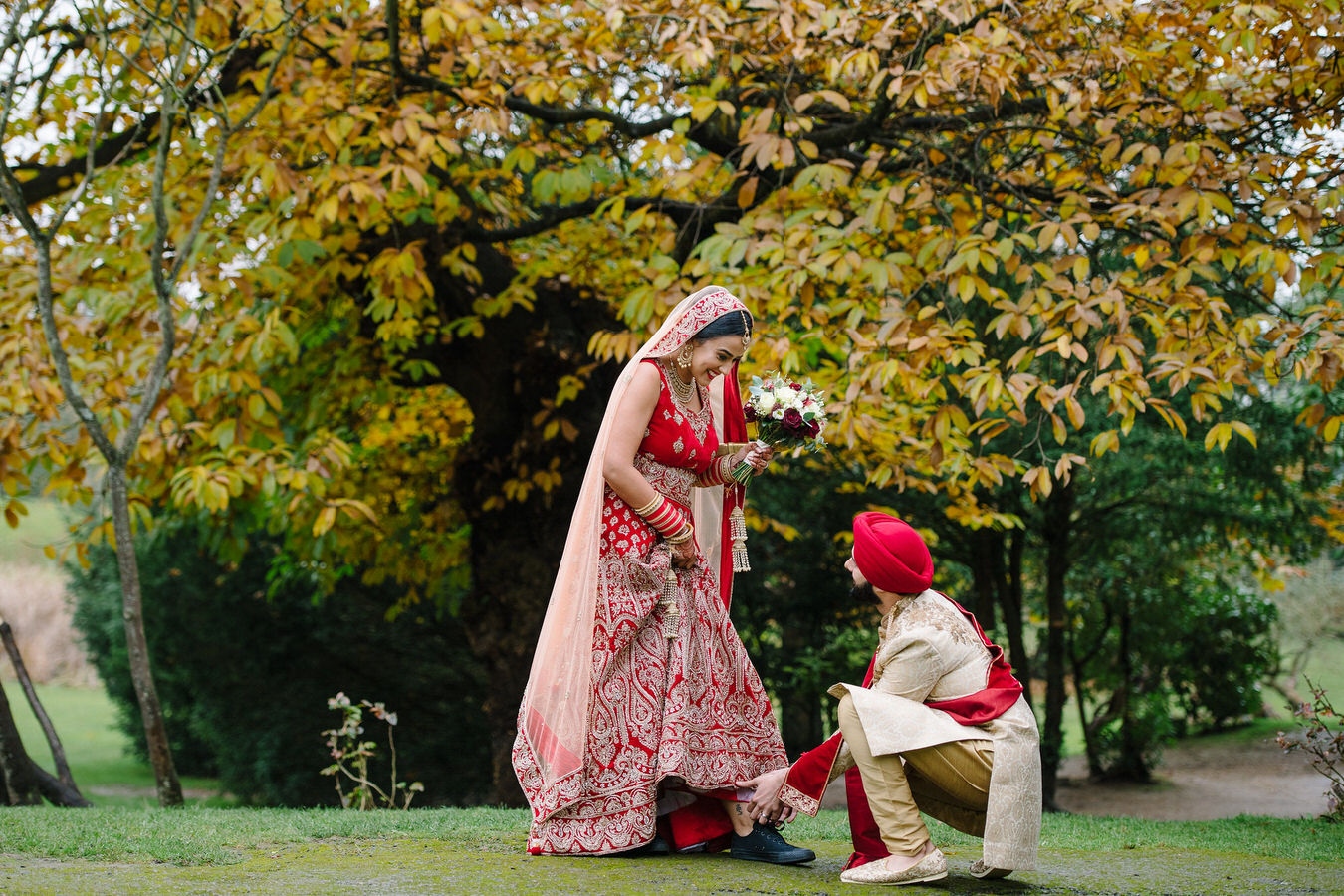 Asian groom tying bride's black Converse shoes in the grounds at Hampton Court House looking autumnal as captured by Asian Sikh wedding photographer.