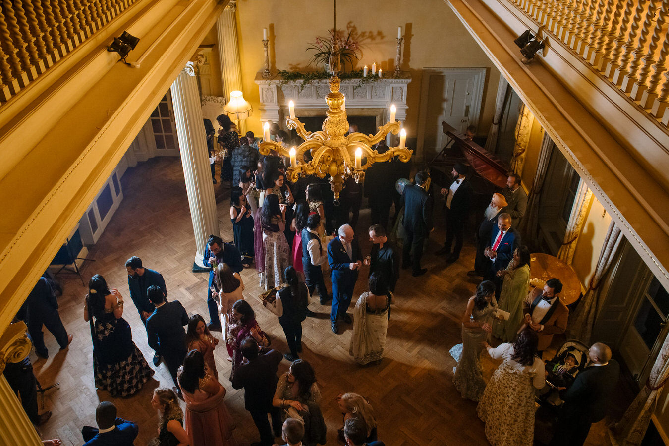 Photo taken from the first floor looking down to wedding guests chatting and feeling good during wedding reception at Hampton Court House.