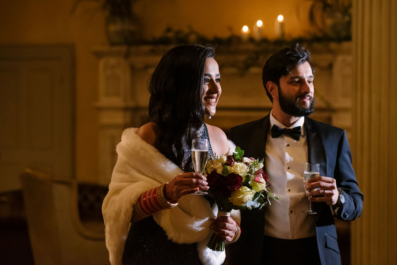 Asian bride with a white fur shawl and groom with black smoking suit, having champagne glasses in hands are having fun.