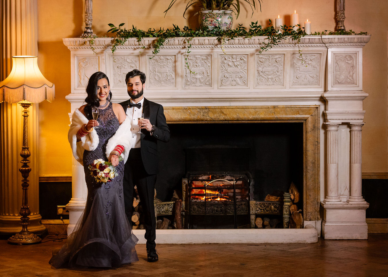 Asian bride in a grey long evening dress & white fur cape holding a red & white flower bouquet in her hand and groom dressed in a black smoking suit staying in front of the fireplace at Hampton Court