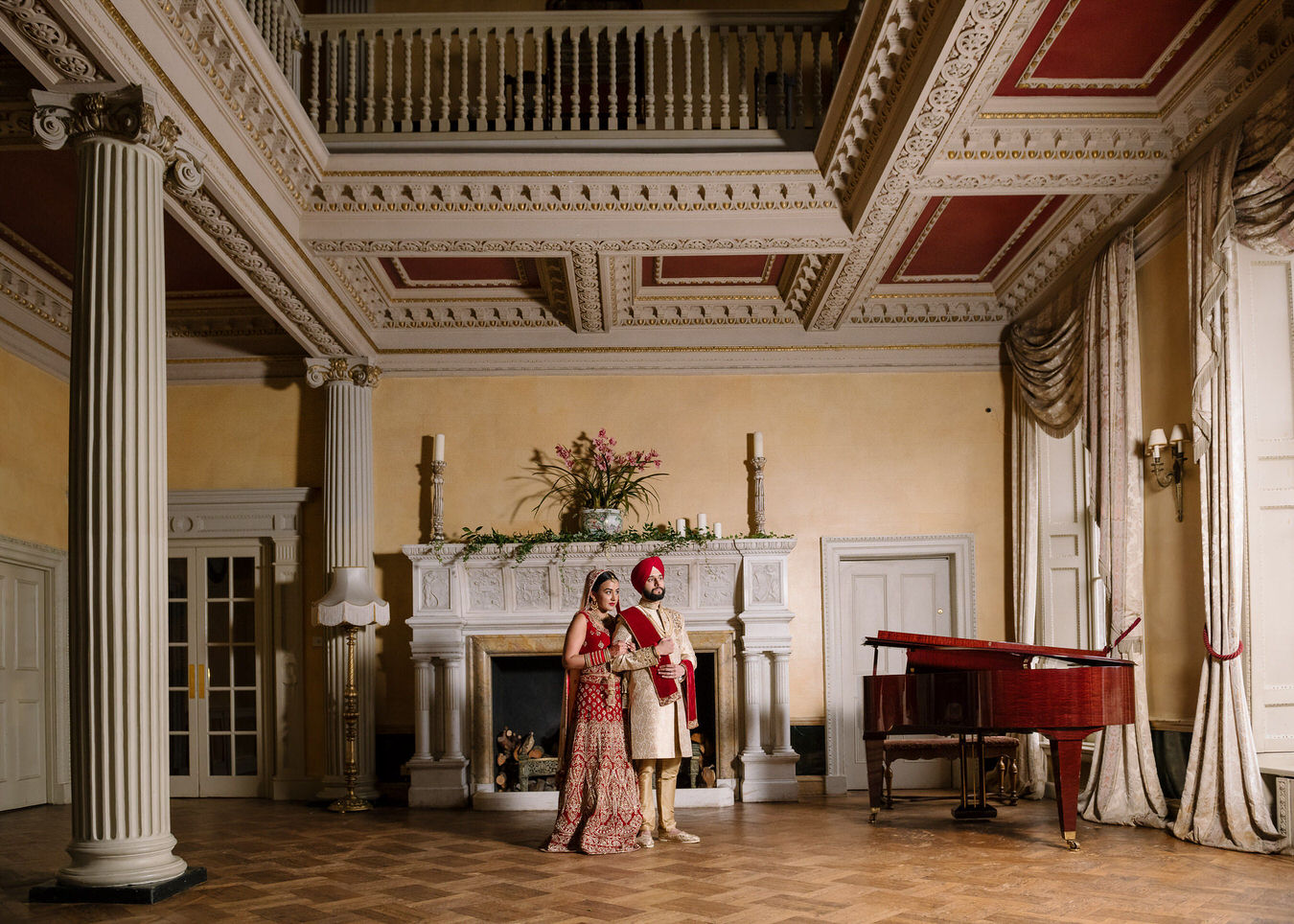 Sikh Asian wedding bride and groom close to each other in front of a white stone fireplace decorated with candles and flower pots at Hampton Court House