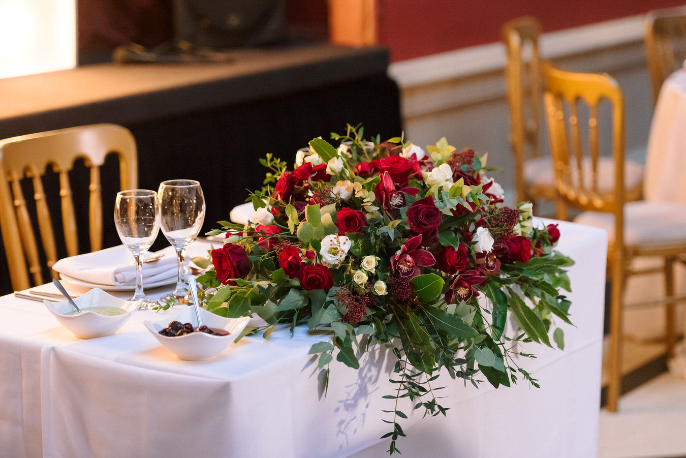 Sweetheart table setting with a winter red and white flower arrangement, a couple of glasses and white napkins
