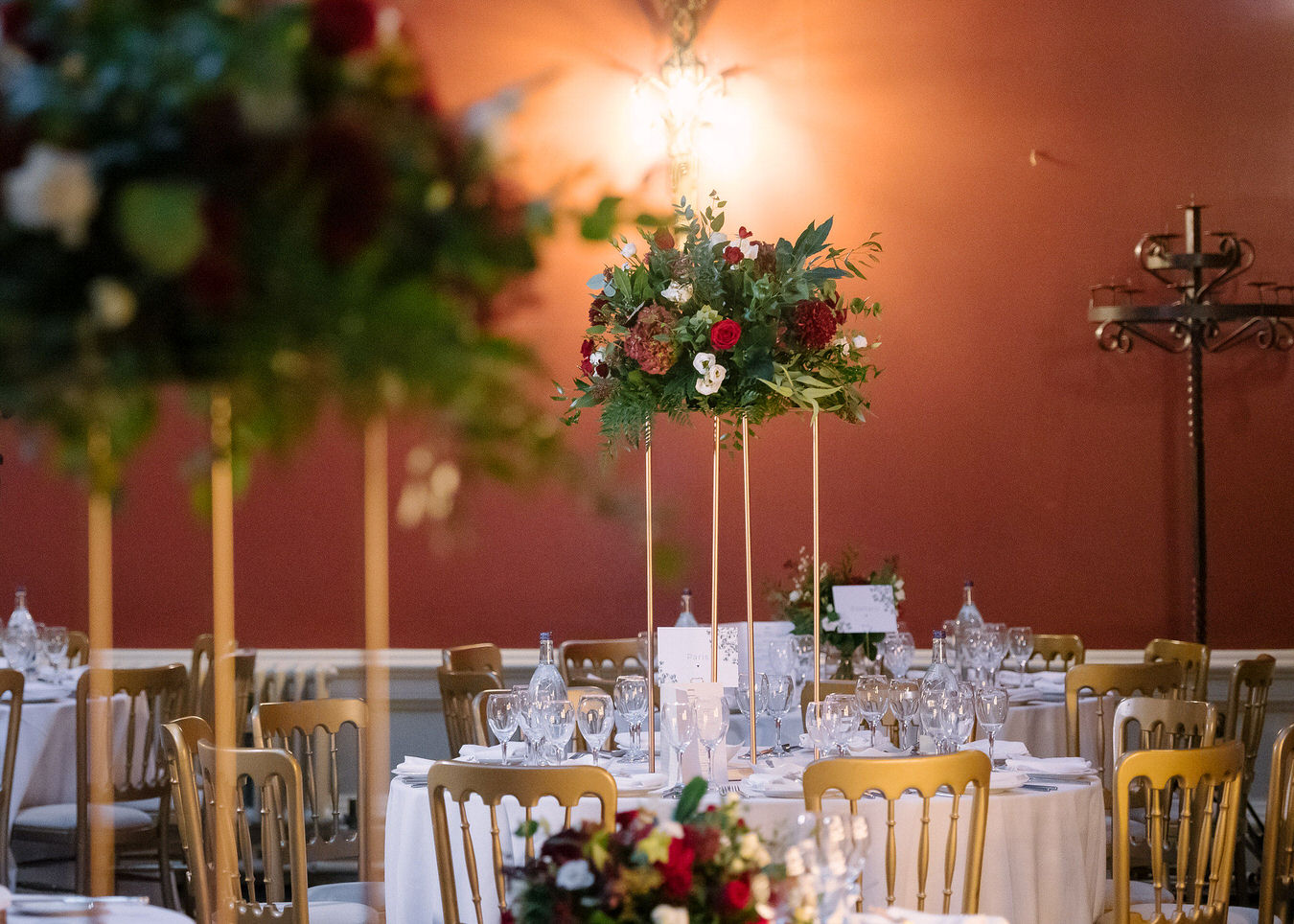 Asian wedding tall table centerpiece with dark red & white flowers at Hampton Court House reception