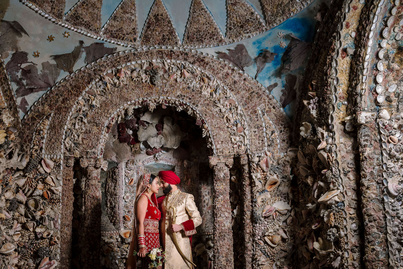 Bride and groom in Sikh Asian wedding standing face to face in the shell grotto at Hampton Court House.