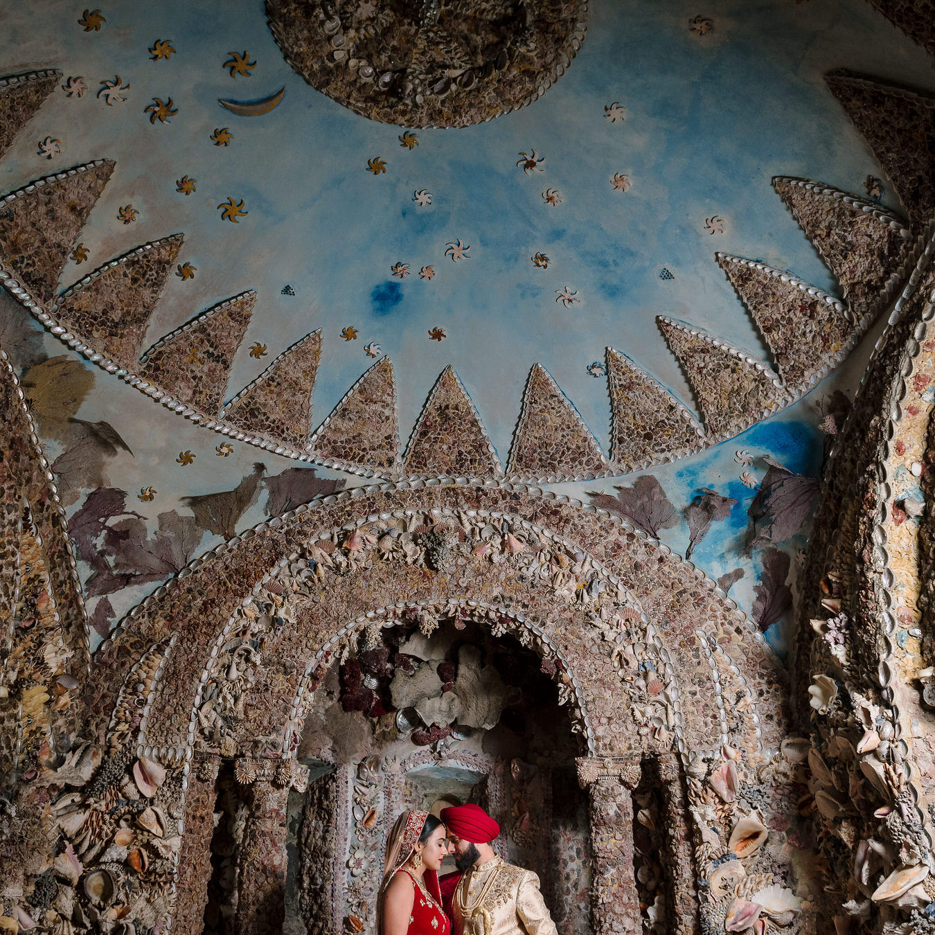 Sikh Asian wedding photographs inside the Hampton Court House shell grotto showing a blue sky with stars and moon made out of shells.