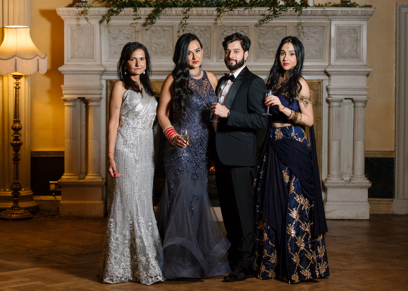 Sikh Asian wedding family photography portrait with mother of the bride dressed in sparkling grey evening dress and sister's bride on the right