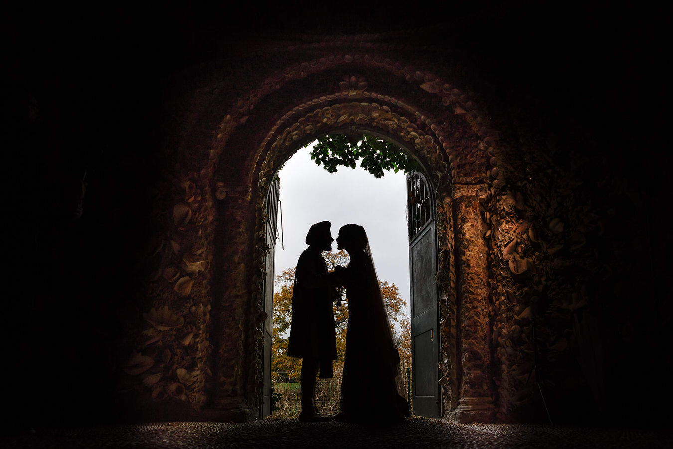 Wedding photography silhouette of bride and groom standing inside the grotto at Hampton Court House