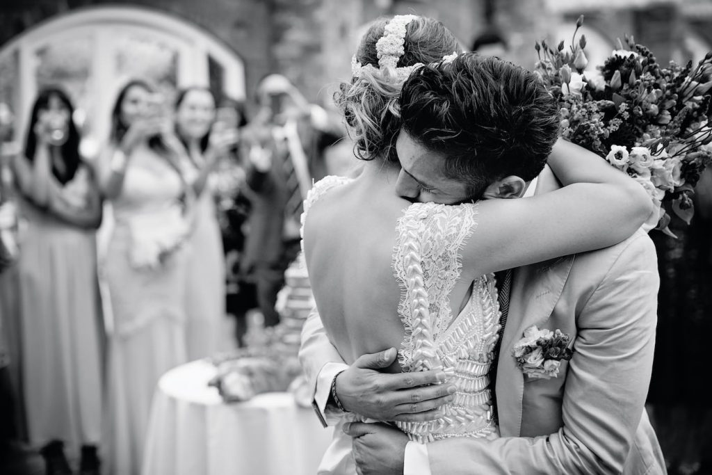 Bride and groom hug in front of their guests