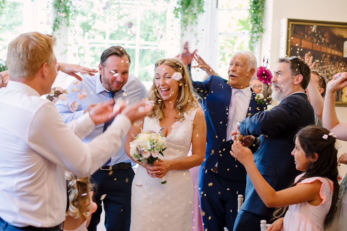 Bride and groom confetti throw after ceremony