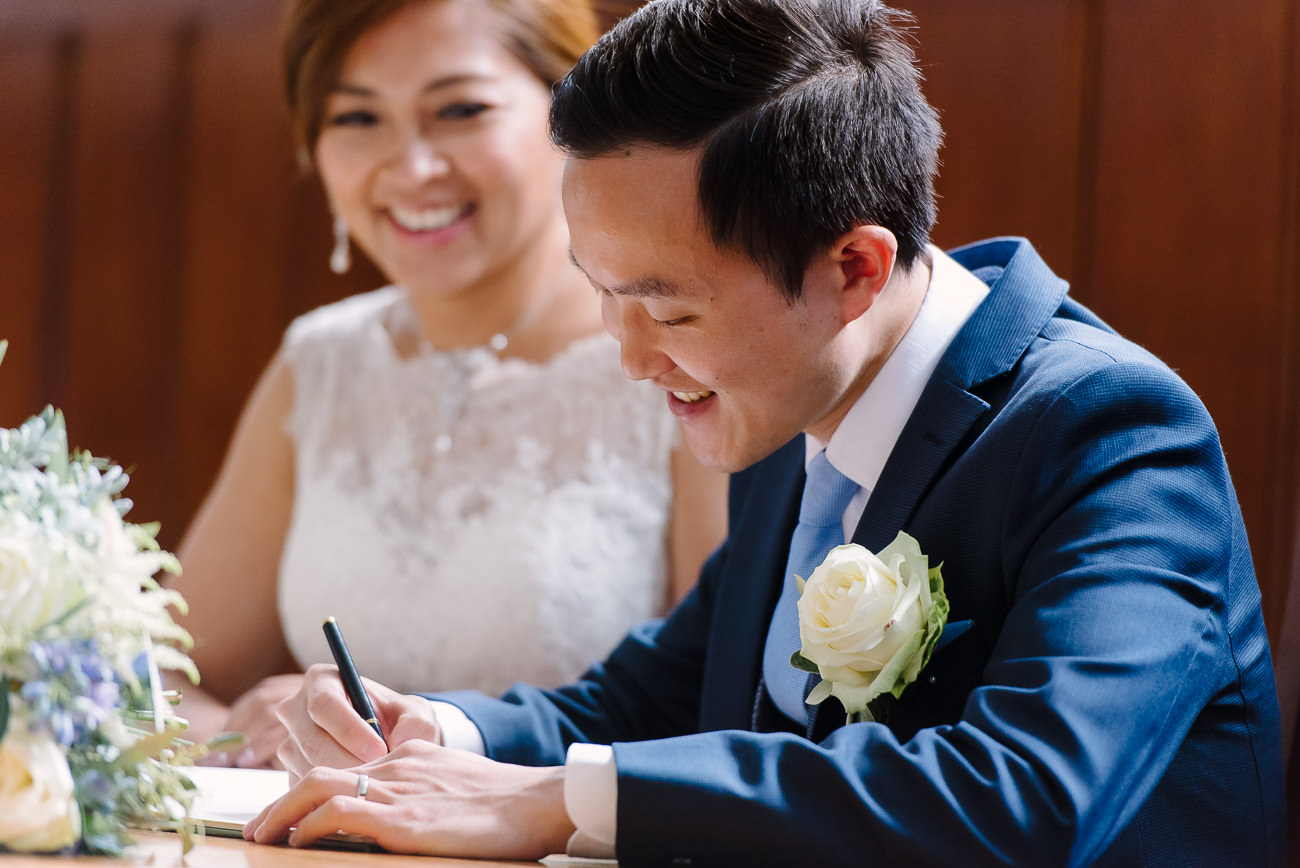 Bride and Groom signing the registry at Guildhall Kingston Upon Thames