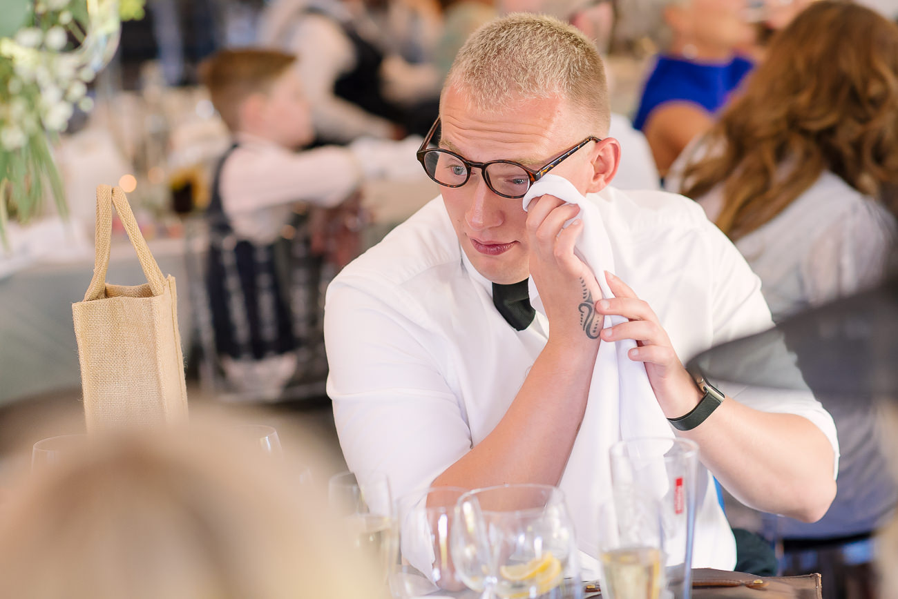 Wedding guest wiping a tear off at speeches
