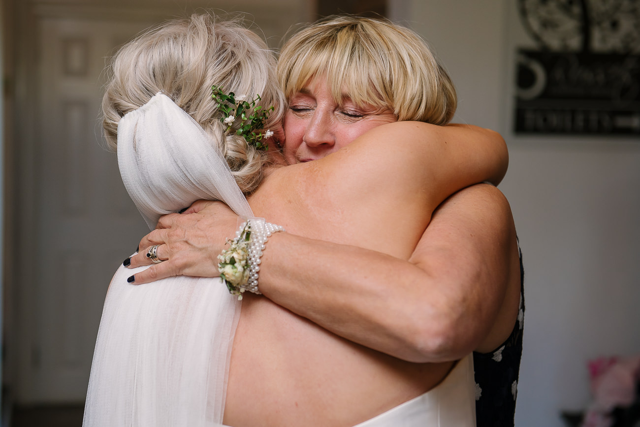 Mother of the groom emotional hugging the bride after after speeches at Russets Country House