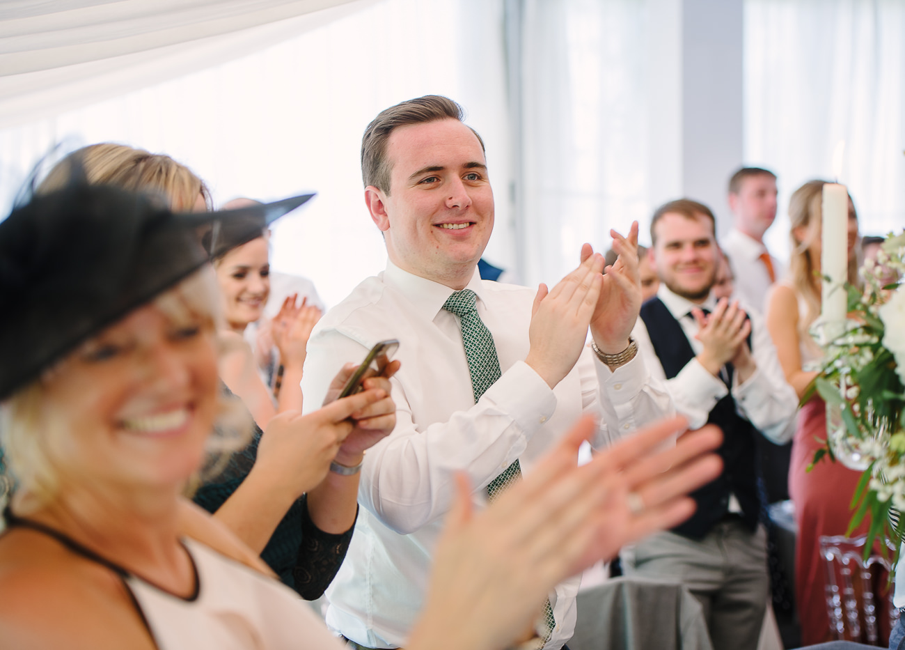 Wedding guests clapping hands for bride and groom entrance