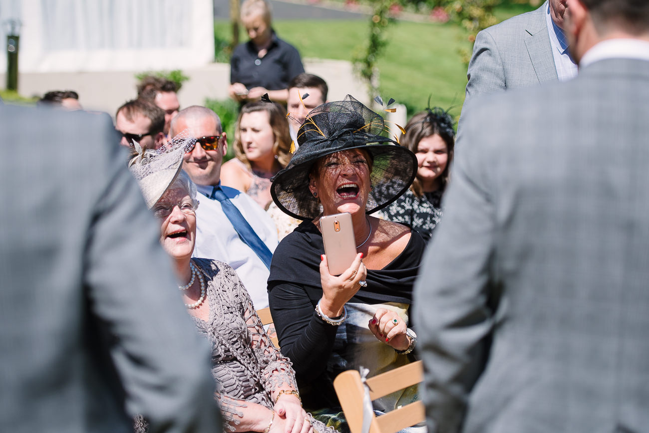 Wedding guest with black hat laughing