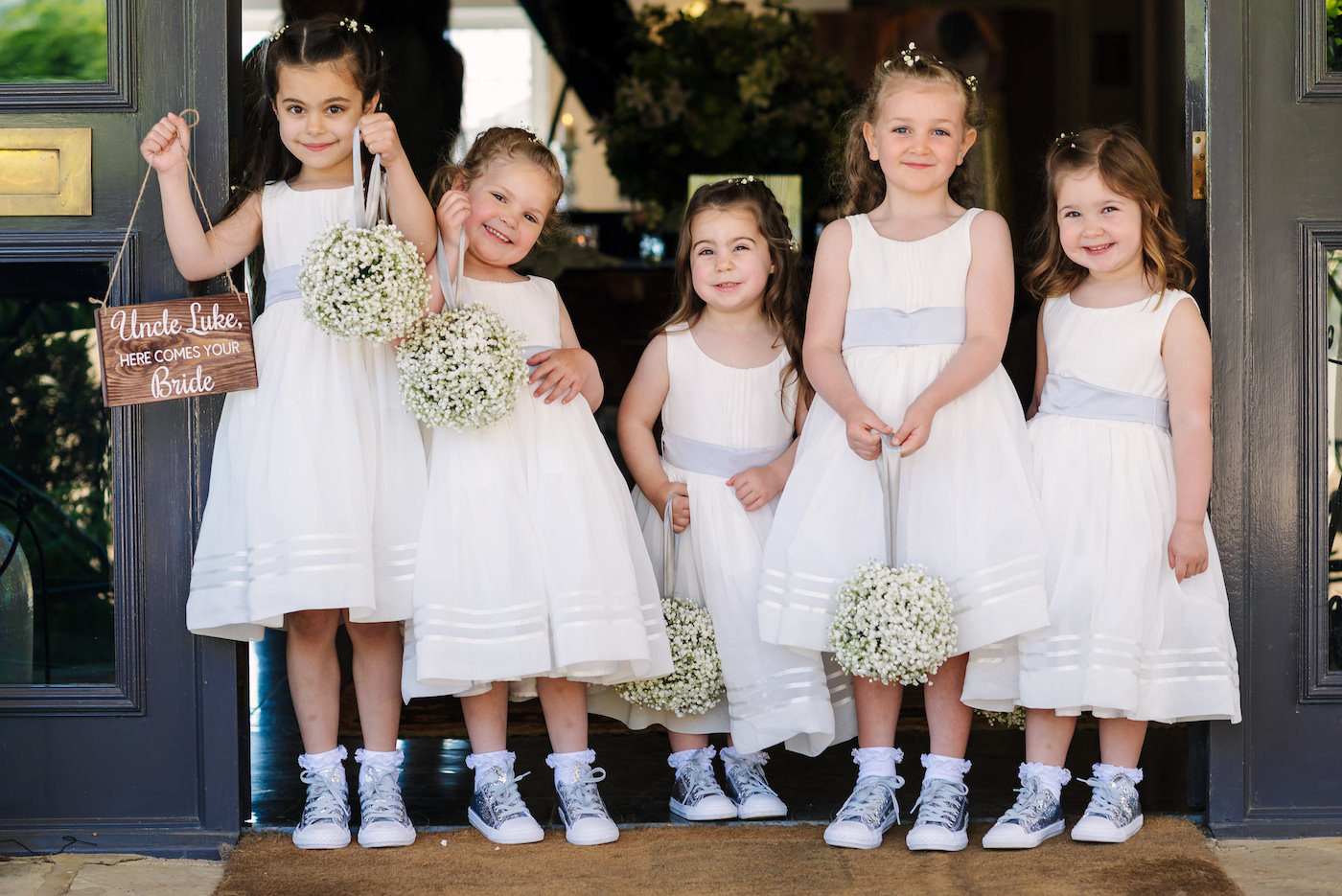 Five flower girls in white dresses holding white baby breath gypsophila pomanders