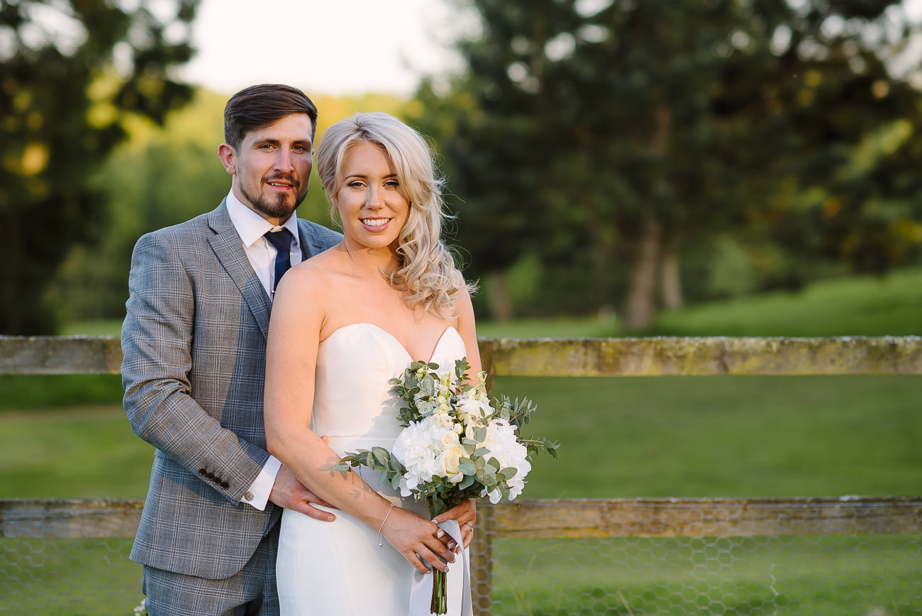 Bride with bouquet and groom standing close and posing at Russets Country House