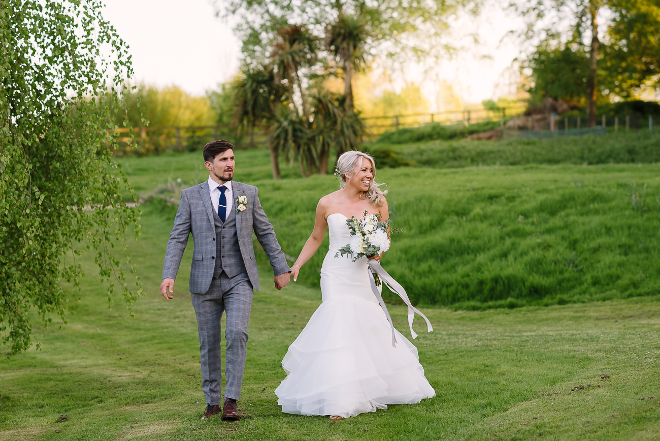 Bride and groom walking on lawn at Russets Country House