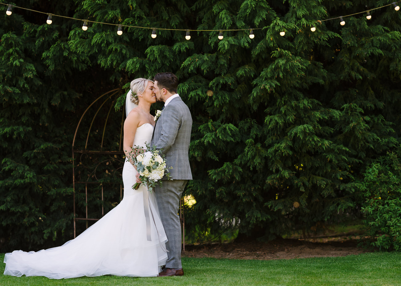 Bride with bouquet and groom kissing portrait at Russets Country House