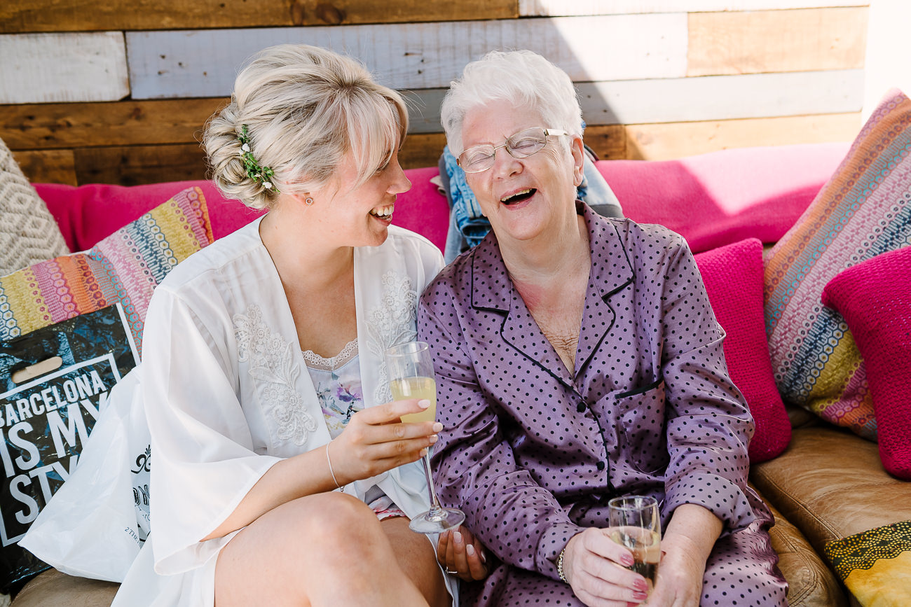 Bride with grandmother having fun during wedding preps