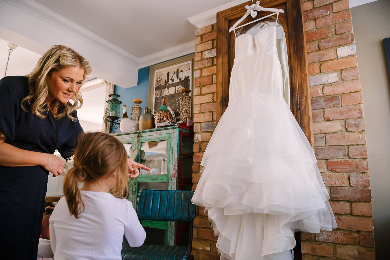 Flower girl is being shown the wedding dress