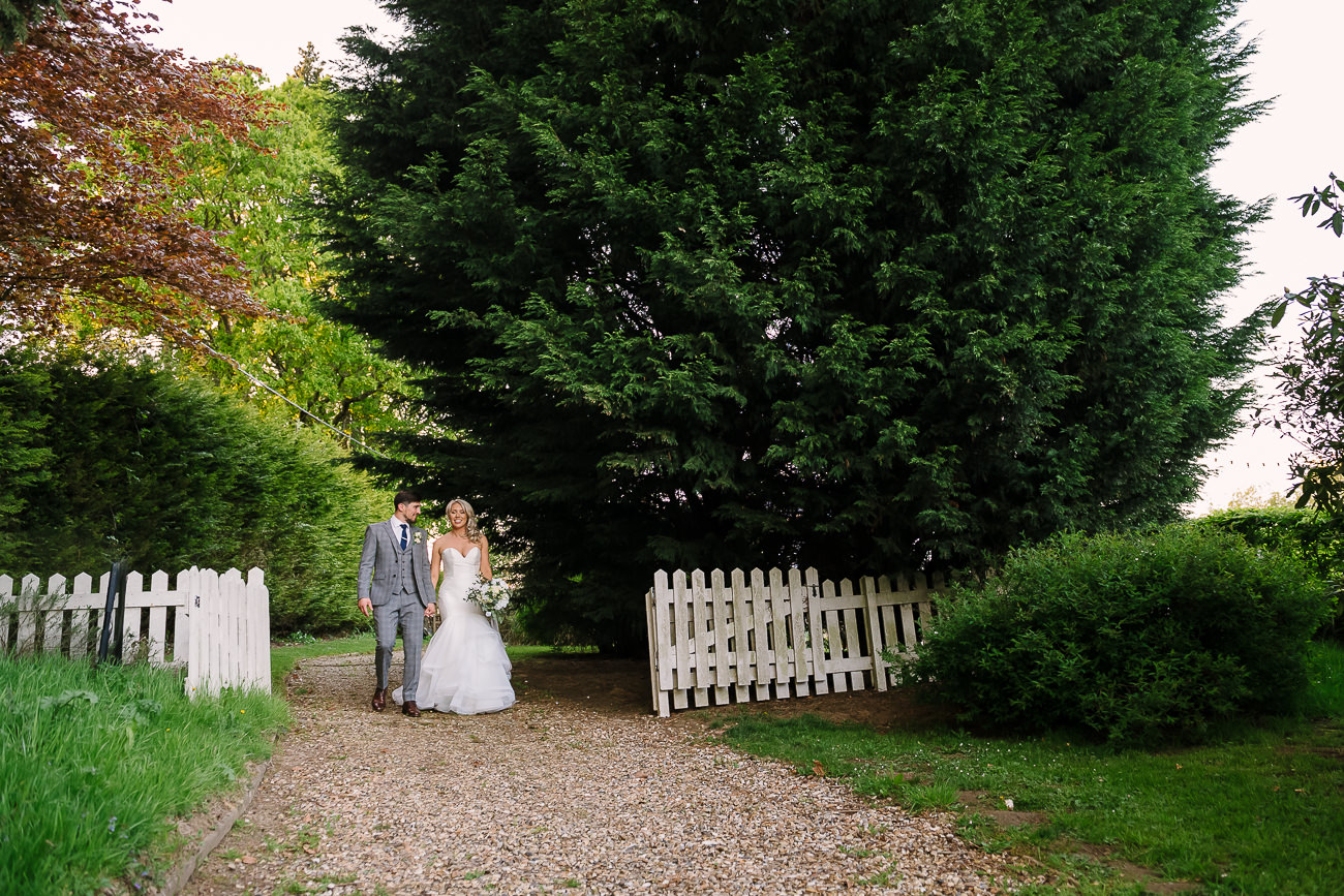 Bride and groom holding hands and walking through the grounds at Russets Country House