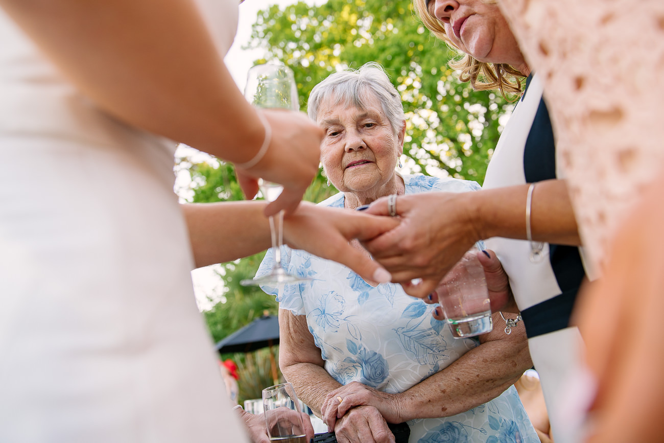 Grandmother looking at brides ring on the finger