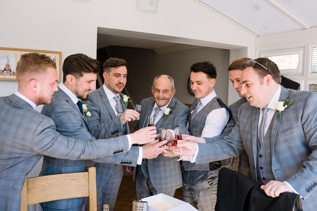 Groom and groomsmen having a toast before they leave to ceremony