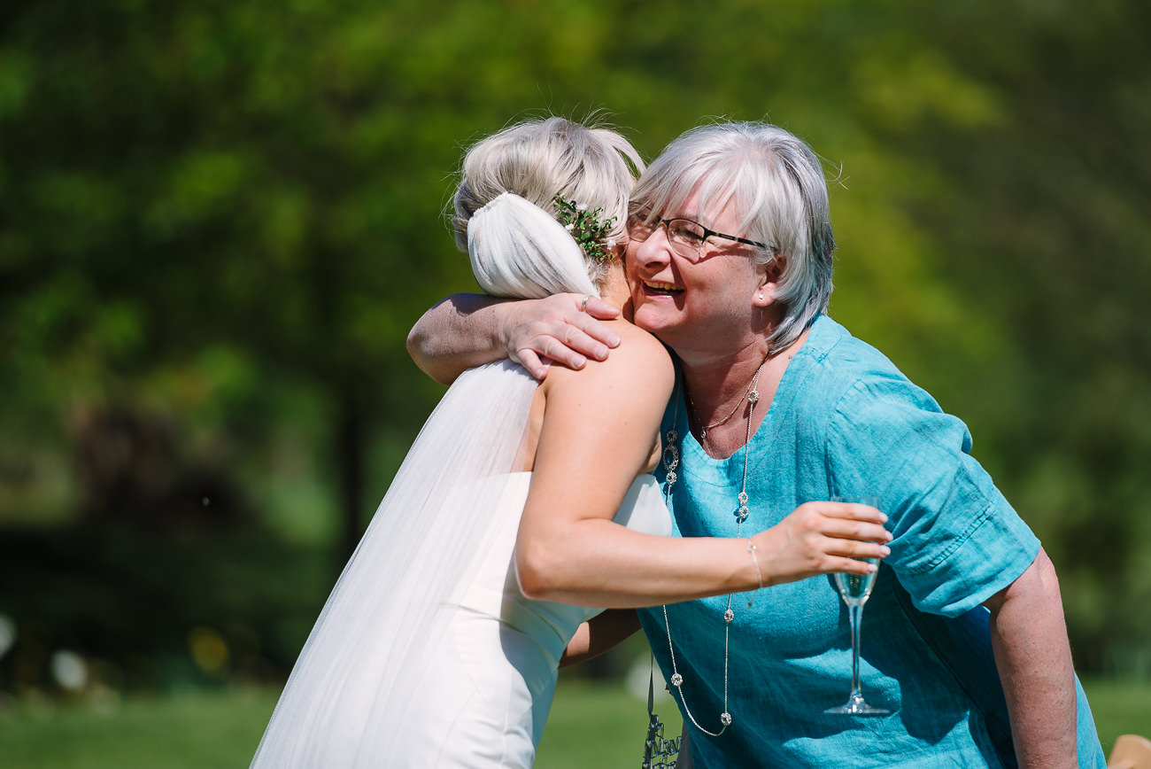 Russets country house owners hugging the bride on the lawn