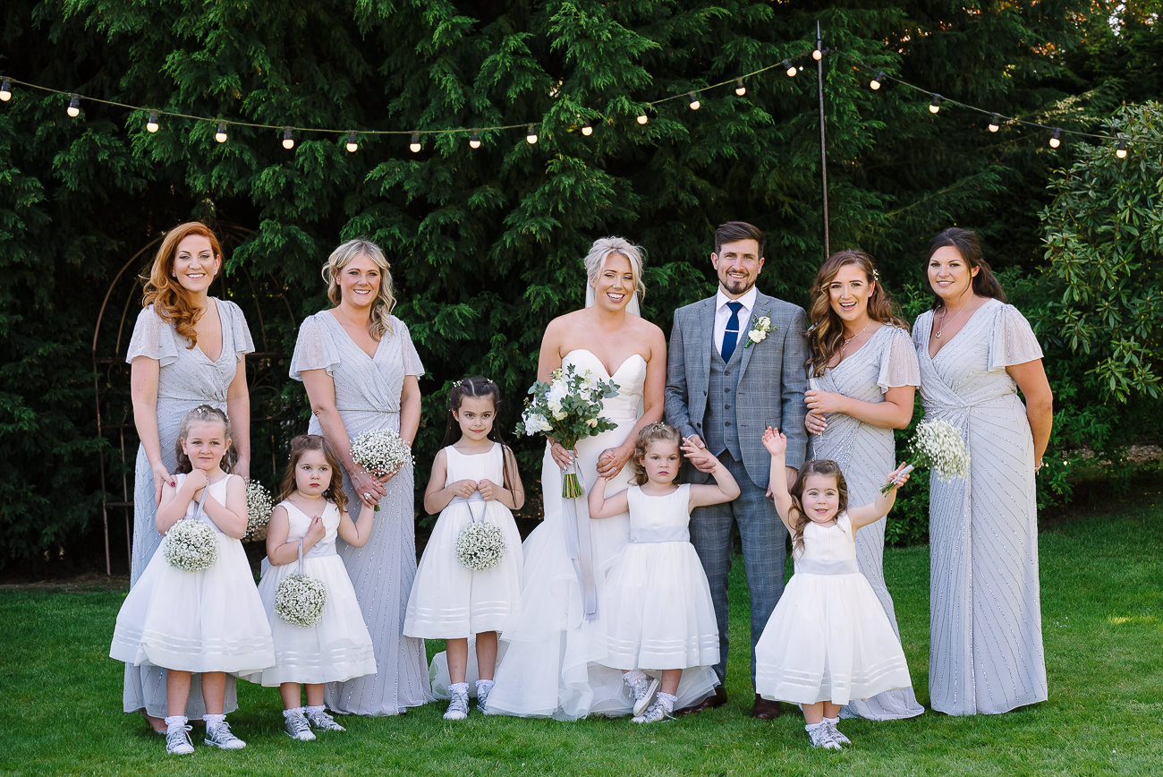 Bridesmaids with flower girls along with bride and groom group photography